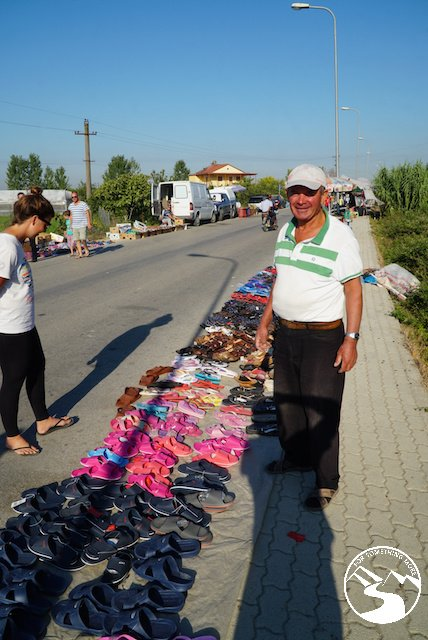 An Albania man selling flip flops at the roadside market