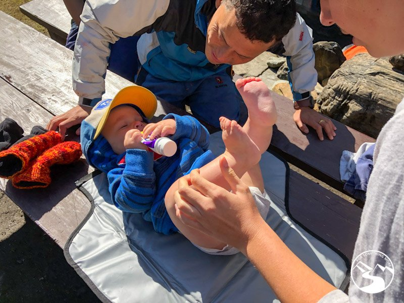 changing a baby's diaper while family trekking Nepal