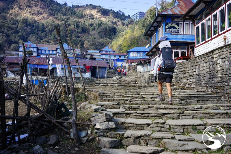 man carries baby while family trekking in Nepal