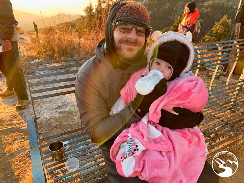 man feeds baby a bottle at the summit of Ghorepani Poon Hill