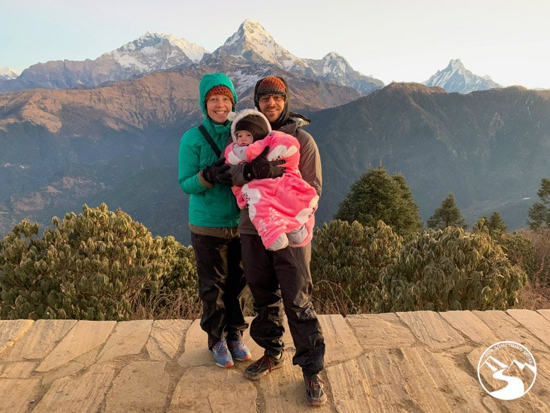 family poses for photo at the summit of Ghorepani Poon Hill