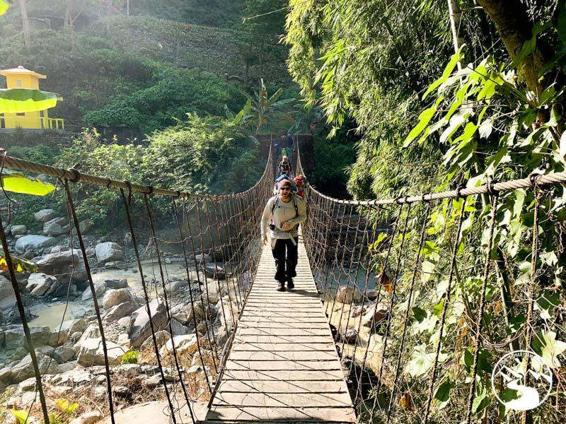 Many carries baby in baby hiking backpack across suspension bridge on a Ghorepani Poon Hill Trek