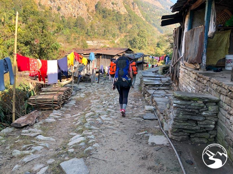 woman hiking through Nepalese village