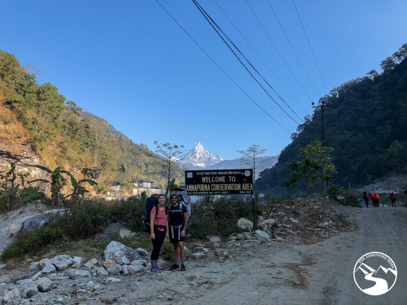 man and woman posing for photo near the entry sign to the Annapurna Conservation Area
