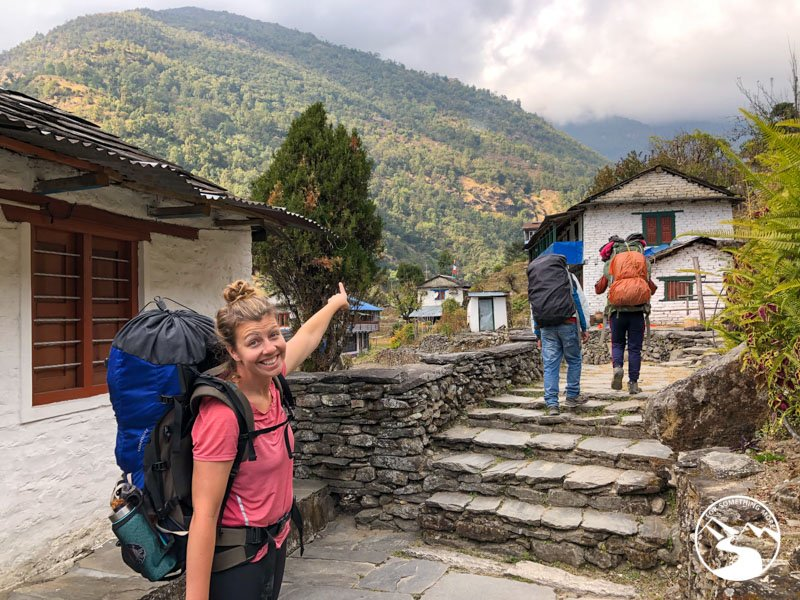 woman points uphill to Ulleri on a Ghorepani Poon Hill Trek