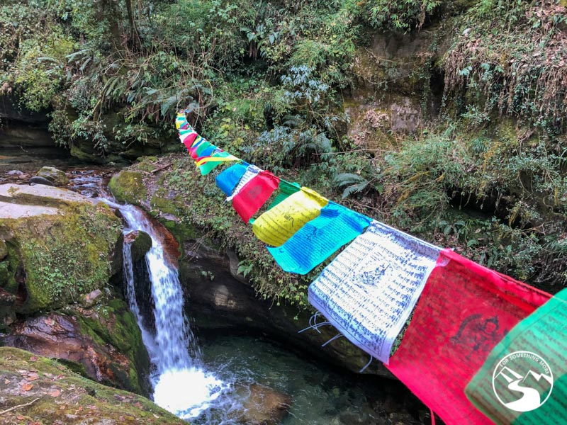 prayer flags draped across a river and waterfall