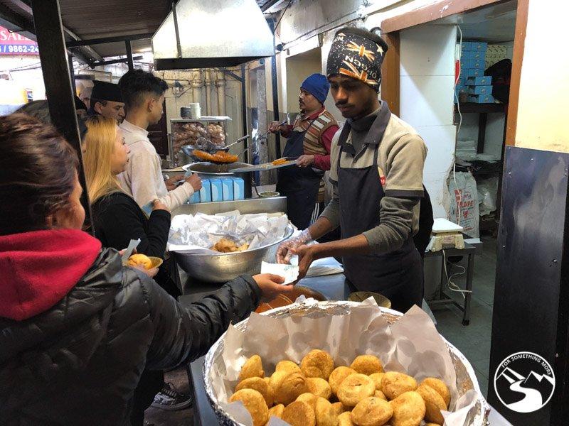 a man serving samosas on our Nepal street food tour