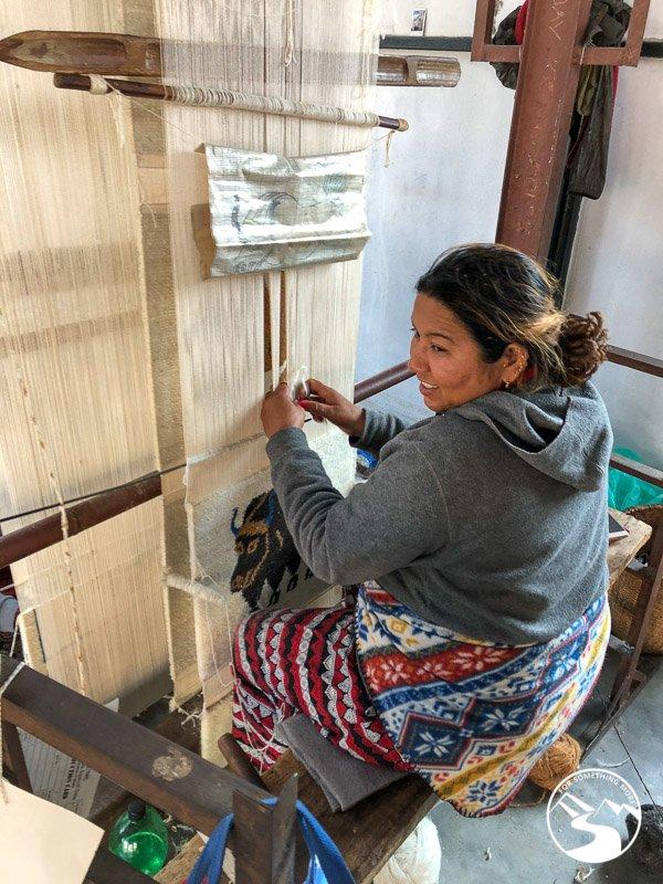 a woman weaving a carpet