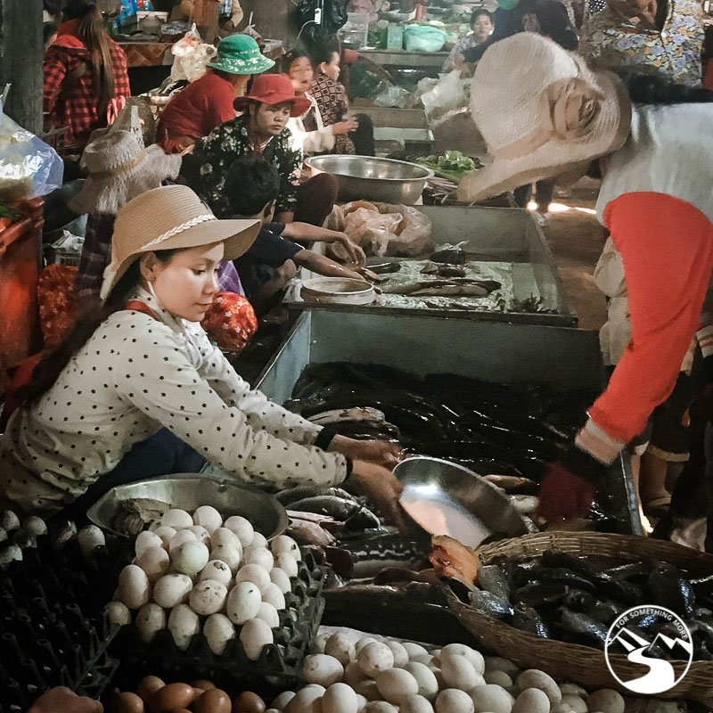 A woman in the market sells fresh live fish