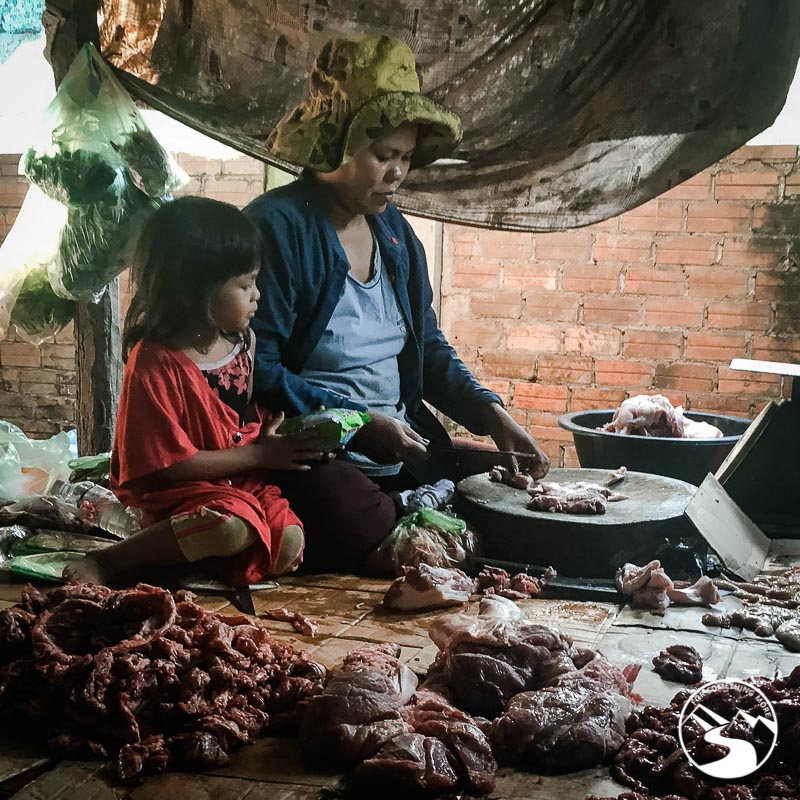 a woman in the market selling meat
