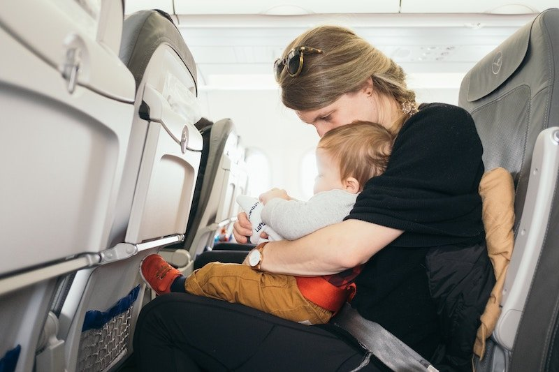 a mother sitting on an airplane seat flying with a toddler
