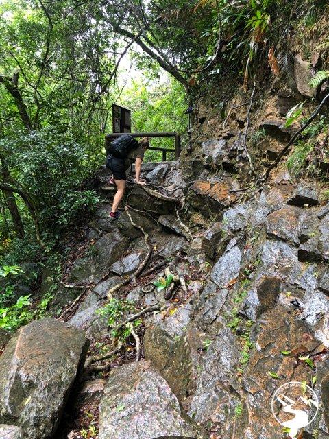 woman climbing on slippery rocks