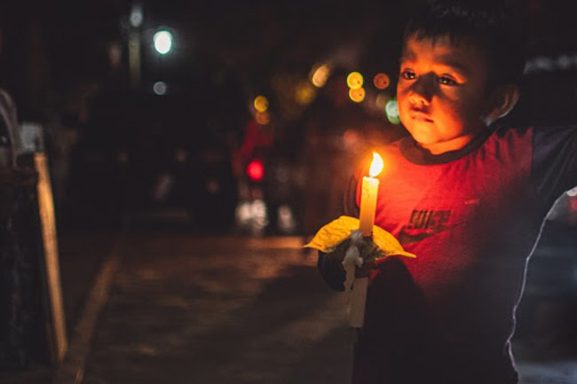 boy holding candles
