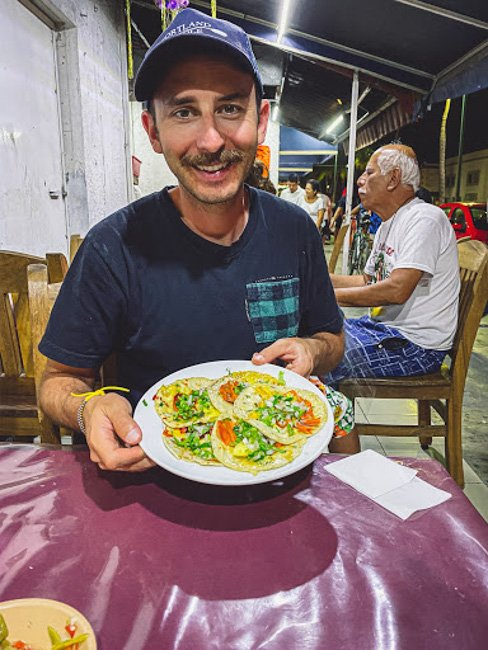 man holding plate of street food