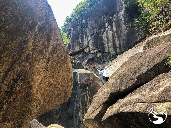 A man rock climbing on the wall above Tai Shui Hang Waterfall
