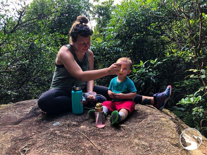 mom feeding son on hiking trail