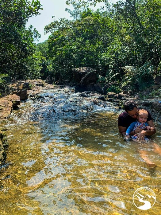 father and son swimming in stream