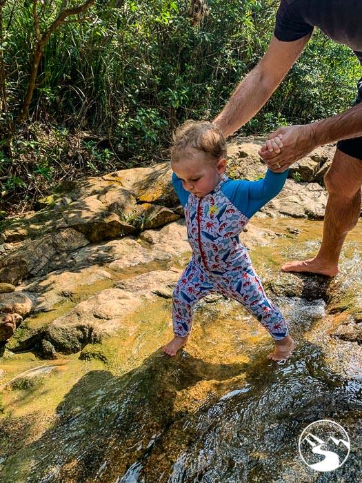 boy wearing sun suit in stream