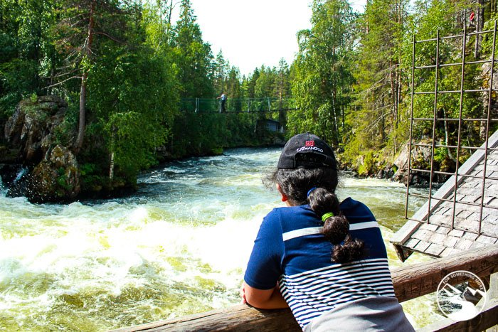 girl standing near the waterfall next to Myllykoski during one of her day trips in Lapland Finland