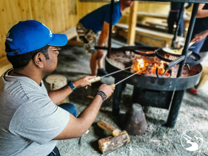 Grilling sausages and marshmallows at the Harrisuvanto camp during on of the day trips in Lapland Finland