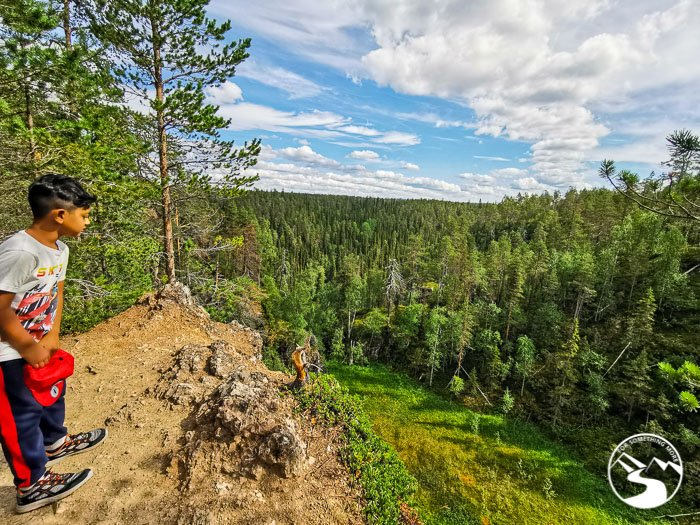 boy looks over one of the cliffs overlooking the Finnish Taiga forests during one of his day trips in Lapland Finland