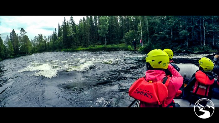 family going through rapids on Kitkajoki River during one of the day trips in Lapland Finland
