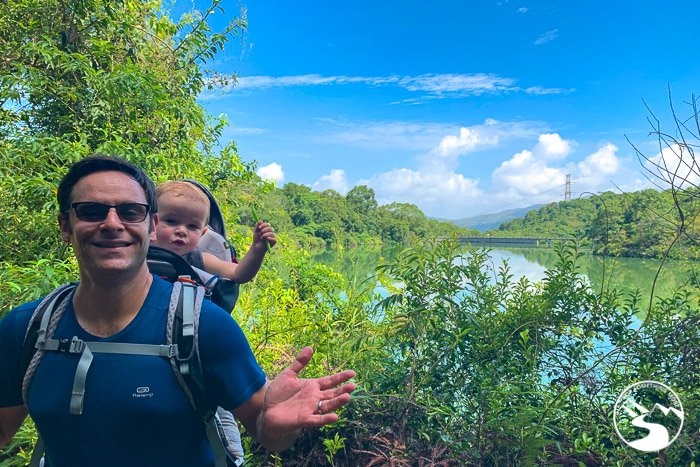 Man hiking with child in Osprey backpack on the Ho Pui Reservoir Family Walk