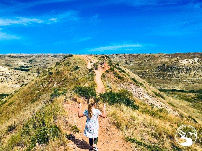 girl hiking on dirt trail