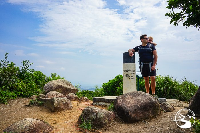 man and son standing at the summit marker for Tai Leng Tung