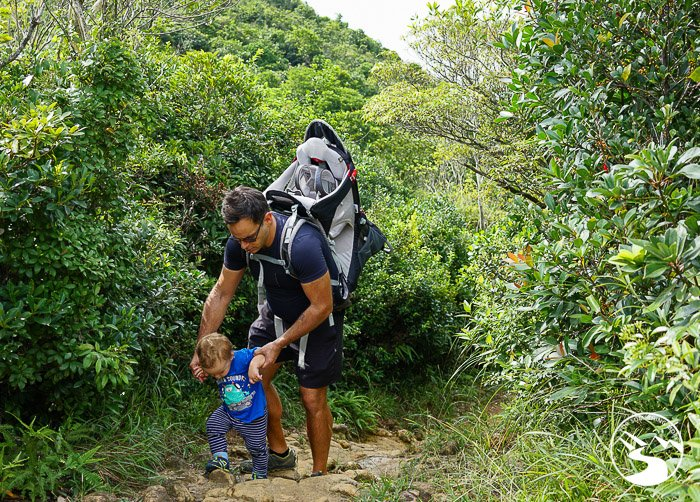 father helping son on a hiking trail near lobster bay