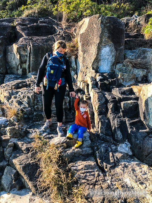 family exploring rocky coastline at siu sai wan promenade