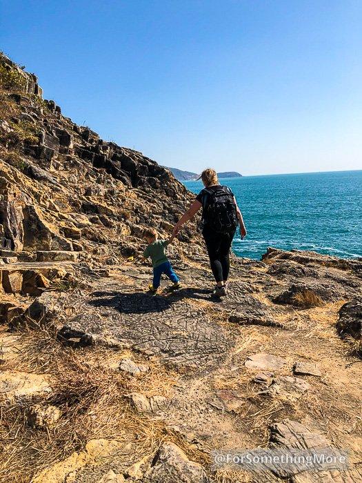 woman and boy walking on rocky coast