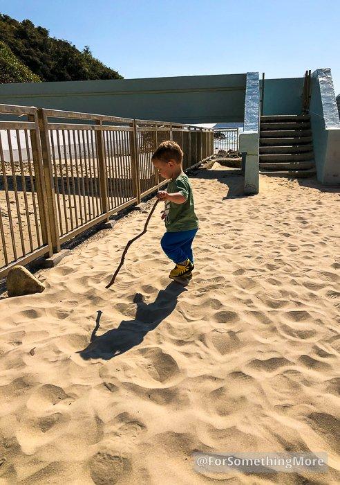 boy playing on big wave bay beach