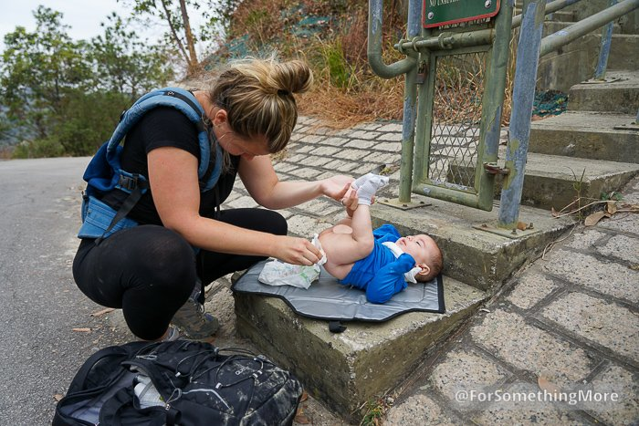 woman changing a baby's diaper while hiking