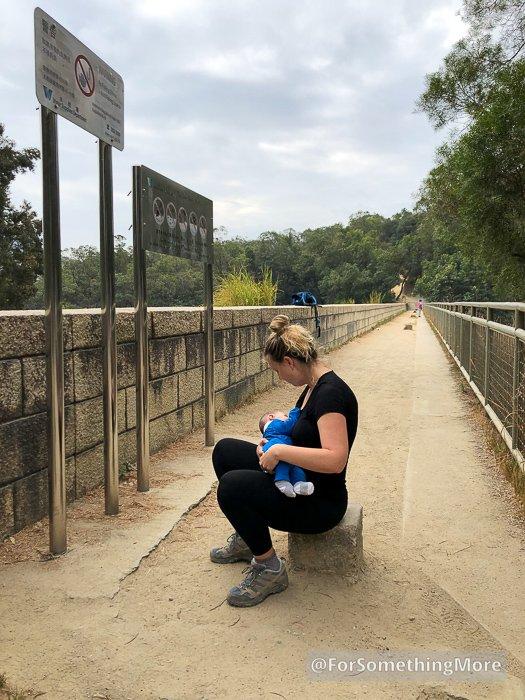 woman nursing a baby while hiking