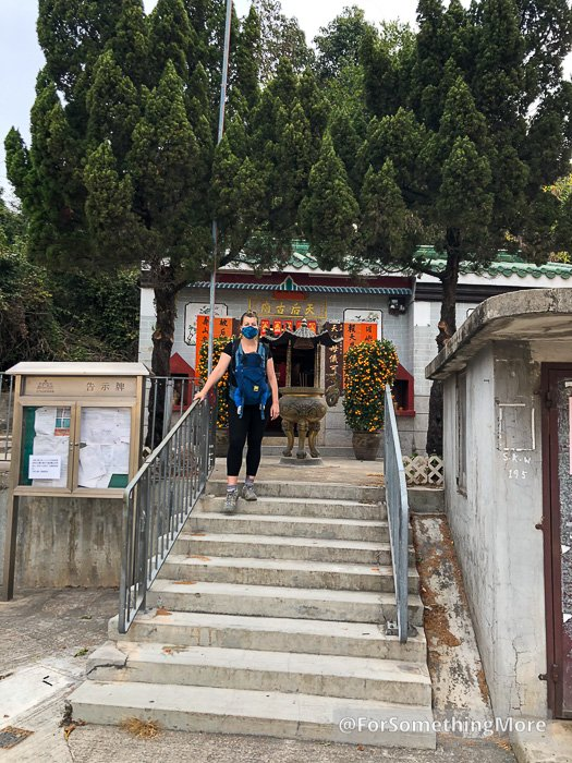 woman standing at the temple in So Kwun Wat Lee Uk Tsuen
