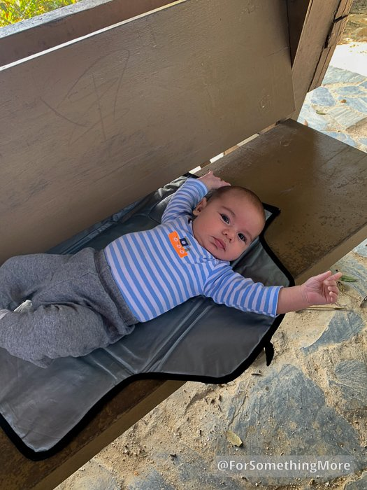 infant laying on changing pad on wooden bench