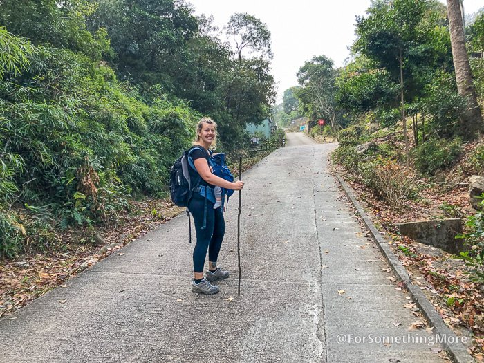 woman hiking with a baby up a hill road