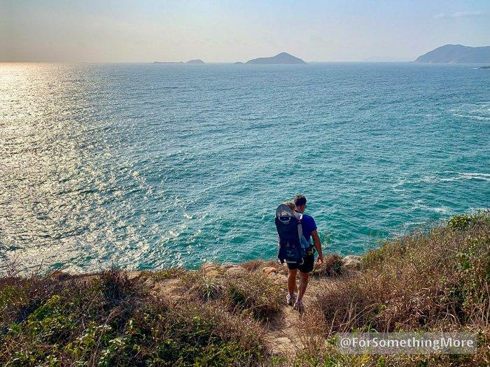 man hiking with son on coast