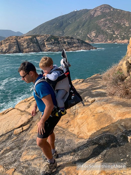 man hiking with son in baby backpack