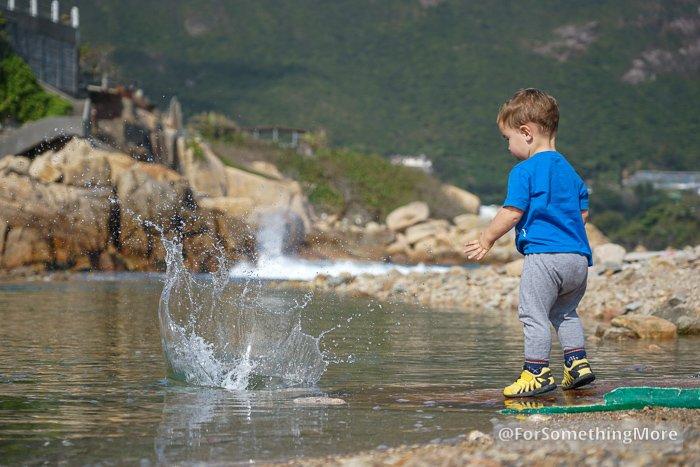 boy throwing rock in water making splash