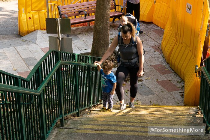 mother hiking up stairs with two sons