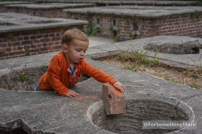 boy putting brick in wartime stove on Quarry Bay Tree Walk (鰂魚涌樹木研習徑)