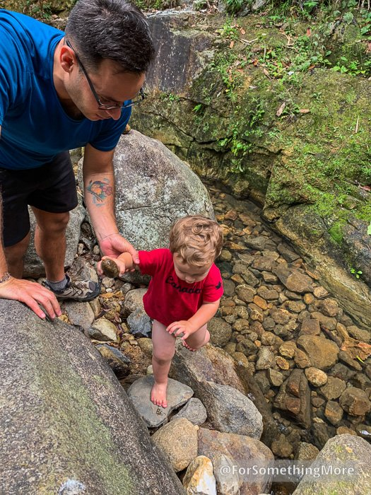 father and son playing in stream