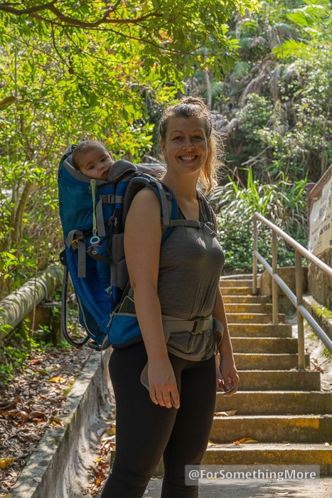 happy mother with baby in hiking backpack