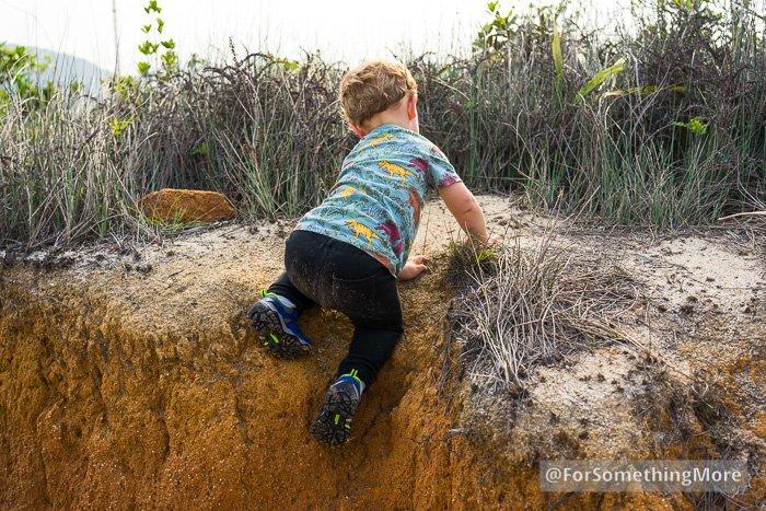 toddler climbing up dirt hill