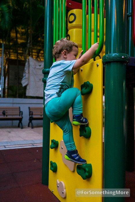 toddler climbing up rock wall