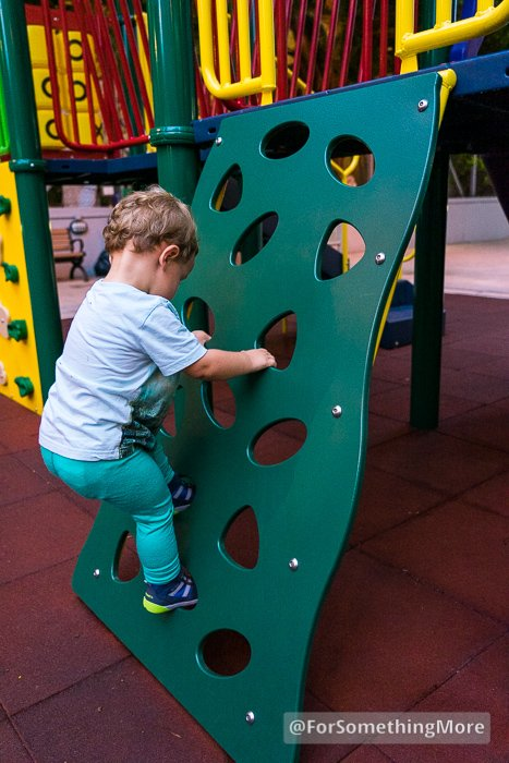toddler climbing on jungle gym