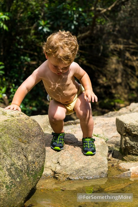 boy using toddler sandals in a stream