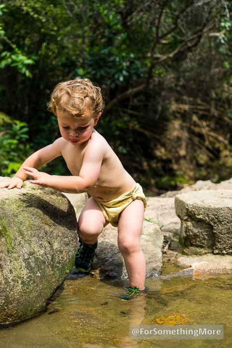 boy stepping in to water with toddler sandals